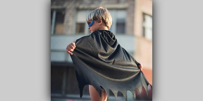 Mały chłopiec wpelerynie super bohatera