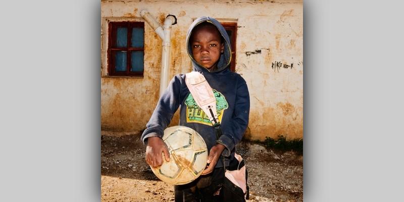 Chłopiec trzymający wręku piłkę